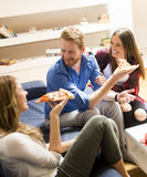Group of friends eating pizza together at home Stock Photography