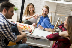 Group of friends eating pizza together at home. View at group of friends eating pizza together at home Royalty Free Stock Photos