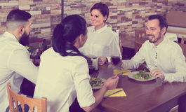 Group of friends eating at restaurant and chatting Royalty Free Stock Photography