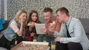 Group of friends eating takeaway pizza and watching programm on tablet stock video
