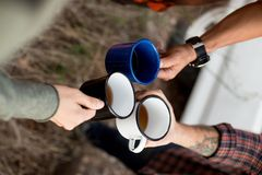 Friends share drink during hiking trip. Group of friends enjoy hot beverage, coffee or tea during hiking or road trip, toast to more adventures and exploration Royalty Free Stock Photo