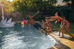 Friends enjoy pool party in summertime. Group of friends enjoy pool party together in summertime. Women pushing male friends in the swimming pool Royalty Free Stock Photos