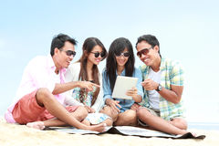 Group Friends Enjoying Beach Holiday together with tablet pc Royalty Free Stock Photos
