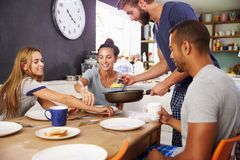 Group Of Friends Enjoying Breakfast In Kitchen Together Royalty Free Stock Image