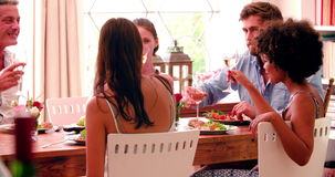 Group Of Friends Enjoying Dinner Party At Home Together. Group of friends at home sitting around table enjoying dinner party together - they make a toast.Shot in stock footage