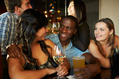 Group Of Friends Enjoying Drink At Bar Together Royalty Free Stock Images