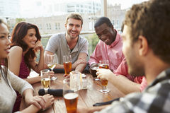 Group Of Friends Enjoying Drink At Outdoor Rooftop Bar Royalty Free Stock Photography