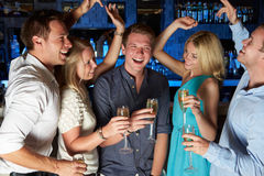 Group Of Friends Enjoying Glass Of Champagne In Bar. Smiling And Laughing Stock Image