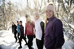 Group of friends enjoying jogging in the snow in winter. A Group of friends enjoying jogging in the snow in winter stock image