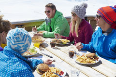 Group Of Friends Enjoying Meal In Cafe At Ski Resort Stock Images