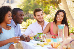 Group Of Friends Enjoying Meal At Outdoor Party In Back Yard Stock Photos
