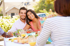 Group Of Friends Enjoying Meal At Outdoor Party In Back Yard Royalty Free Stock Photo