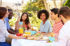 Group Of Friends Enjoying Meal At Outdoor Party In Back Yard Stock Image