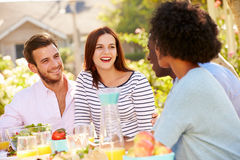 Group Of Friends Enjoying Meal At Outdoor Party In Back Yard Royalty Free Stock Image