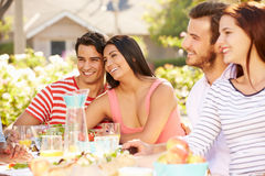 Group Of Friends Enjoying Meal At Outdoor Party In Back Yard Royalty Free Stock Photos