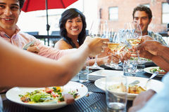 Group Of Friends Enjoying Meal At Outdoor Restaurant Royalty Free Stock Image