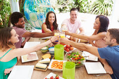 Group Of Friends Enjoying Meal Outdoors At Home Royalty Free Stock Photo