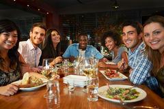 Group Of Friends Enjoying Meal In Restaurant. Smiling To Camera Stock Image