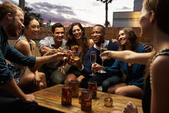 Group Of Friends Enjoying Night Out At Rooftop Bar stock images