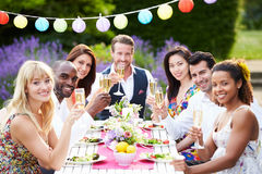 Group Of Friends Enjoying Outdoor Dinner Party. Holding Glass Of Champagne Smiling To Camera Stock Photo