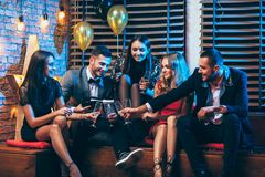 Group of friends enjoying party pouring champagne and having fun Stock Photos