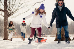 Group of friends enjoying pulling a sled in the snow in winter Stock Images