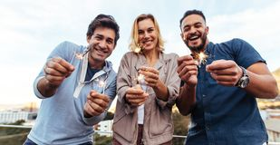 Group of friends enjoying rooftop party with sparklers Royalty Free Stock Photos