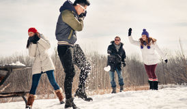 Group of friends enjoying a snowball fight in the snow in winter Royalty Free Stock Images