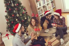 Group of friends exchanging Christmas presents. Group of young friends sitting next to a nicely decorated Christmas tree, exchanging Christmas presents. Focus on stock photos