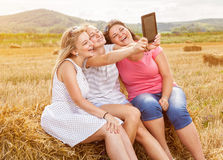 Group of friends in a field taking a picture with a tablet Stock Photo