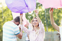 Group of friends floating chinese lanterns Royalty Free Stock Images