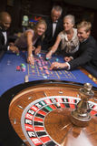 Group of friends gambling in casino. Group of friends gambling at roulette table in casino Stock Photo