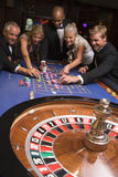 Group of friends gambling in casino. Group of friends gambling at roulette table Royalty Free Stock Photo