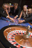 Group of friends gambling in casino. Group of friends gambling at roulette table in casino Royalty Free Stock Photography