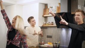Group of friends gathered together at home for a party. Girl throws a piece of food in boys mouth and everyone cheers, fun games stock footage