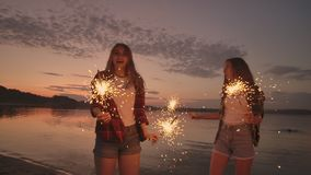 A group of friends girls and men dance on the beach with sparklers in slow motion at sunset. Celebrate new year on the stock video footage