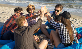 Group of friends giving high five on beach sitting on bean bags. Group of smiling happy friends in sunglasses giving high five gesture on beach sitting on bean royalty free stock images