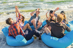 Group of friends giving high five on beach sitting on bean bags. Group of smiling friends in sunglasses giving high five gesture on beach sitting on bean bags royalty free stock photography
