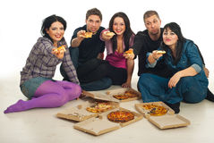 Group of friends giving pieces of pizza Royalty Free Stock Image