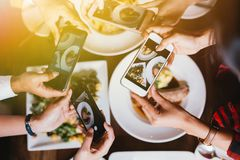 Group of friends going out and taking a photo of Italian food together with mobile phone. Group of friends going out and taking a photo of Italian food together stock photo
