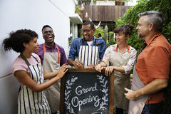 Group of friends with grand opening board together Royalty Free Stock Photography