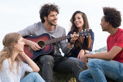 Group Of Friends With Guitar. Group Of Happy Friends With Guitar Having Fun Outdoor Stock Image