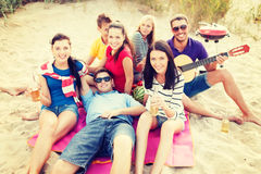 Group of friends with guitar having fun on beach Royalty Free Stock Photo
