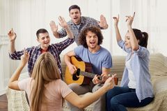 A group of friends with a guitar sing songs at a party indoor. A group of friends with a guitar sing fun songs at a party indoor Stock Photos