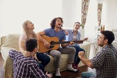 A group of friends with a guitar sing songs at a party indoor. A group of friends with a guitar sing fun songs at a party indoor stock image