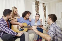 A group of friends with a guitar sing songs at a party indoor. A group of friends with a guitar sing fun songs at a party indoor royalty free stock photography