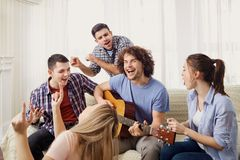 A group of friends with a guitar sing songs at a party indoor. A group of friends with a guitar sing fun songs at a party indoor royalty free stock image