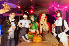 Group of friends in halloween costumes. Having party in the night club stock images