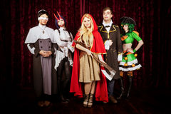 Group of friends in halloween costumes. Friends in halloween costumes posing at club scene stock images