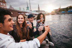 Group of friends hanging out by the lake with drinks Stock Photos